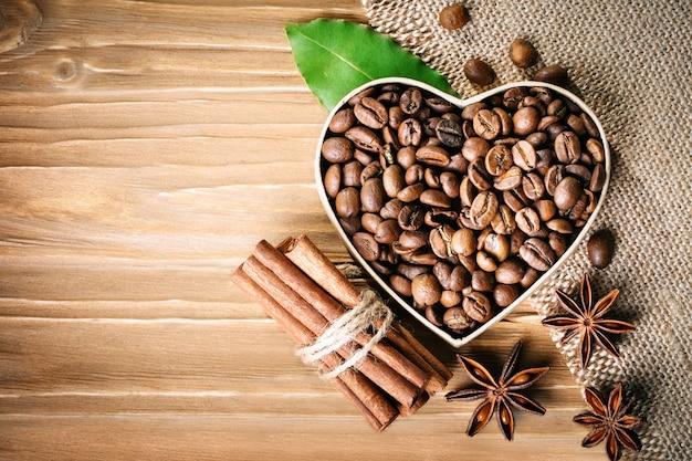 Smażone ziarna kawy leżą w kształcie serca na drewnianych deskach i płótnie.