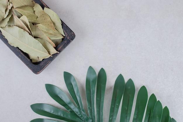 Smażone zielone liście laurowe na drewnianym rustykalnym talerzu.
