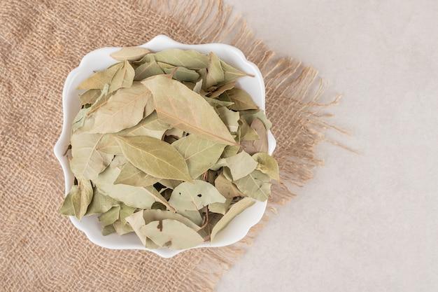 Smażone zielone liście laurowe w ceramicznej filiżance.