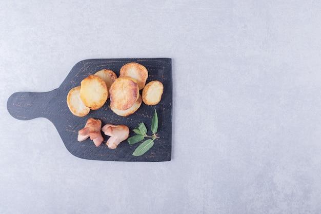 Smażone ziemniaki i kiełbaski na czarnej desce.