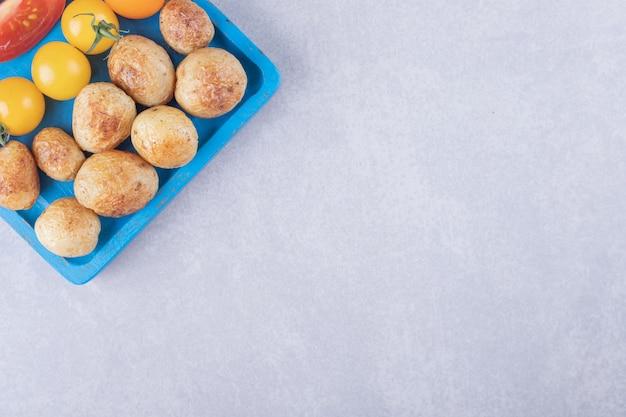 Smażone ziemniaki i pomidory na niebieskim talerzu.