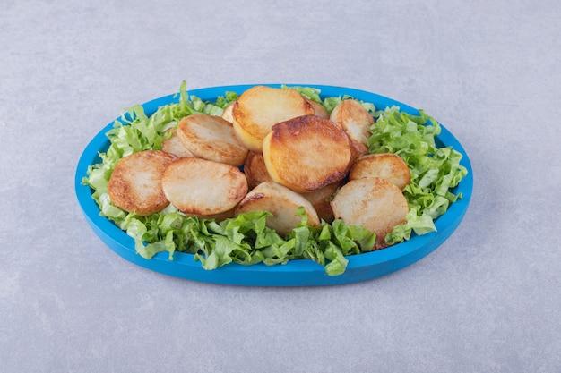 Smażone ziemniaki i sałata na niebieskim talerzu.