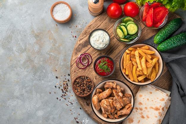 Smażone ziemniaki, kurczak i warzywa oraz sosy na szarej ścianie. lunch, czyli składniki do przygotowania shawarmy, tacos, burritos. fast food.