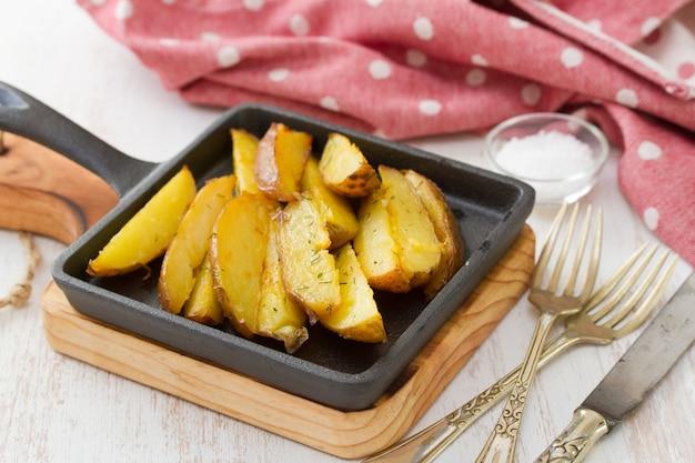 Smażone ziemniaki na czarnej patelni na białym stole