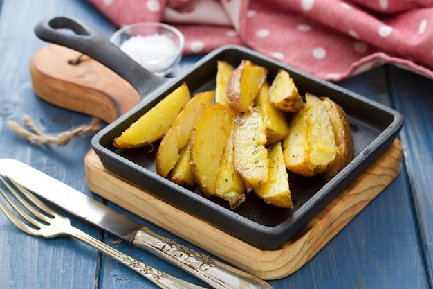 Smażone ziemniaki na czarnej patelni na niebieskim drewnianym stole