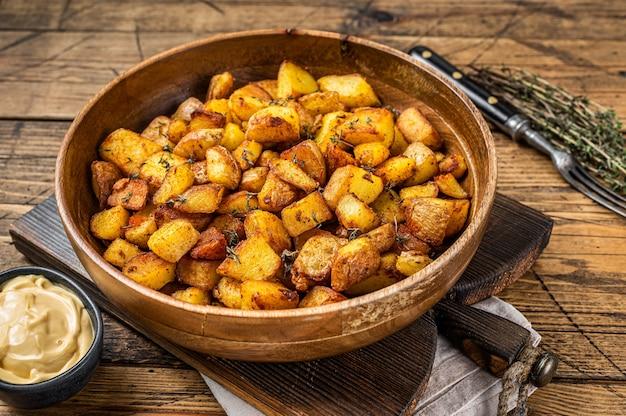 Smażone ziemniaki - patatas bravas tradycyjne hiszpańskie tapas z ziemniakami. drewniane tła. widok z góry.