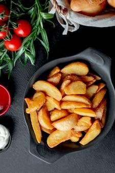 Smażone ziemniaki podawane z keczupem i majonezem
