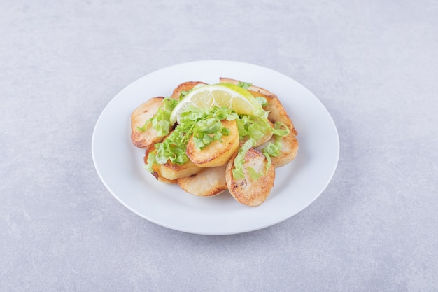 Smażone ziemniaki przyozdobione cytryną na białym talerzu.