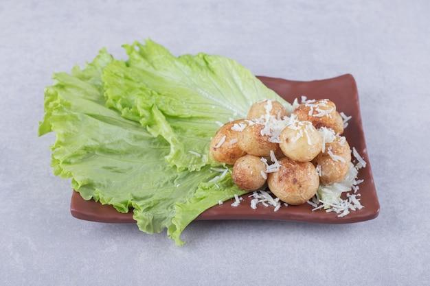 Smażone ziemniaki udekorowane serem na brązowym talerzu.