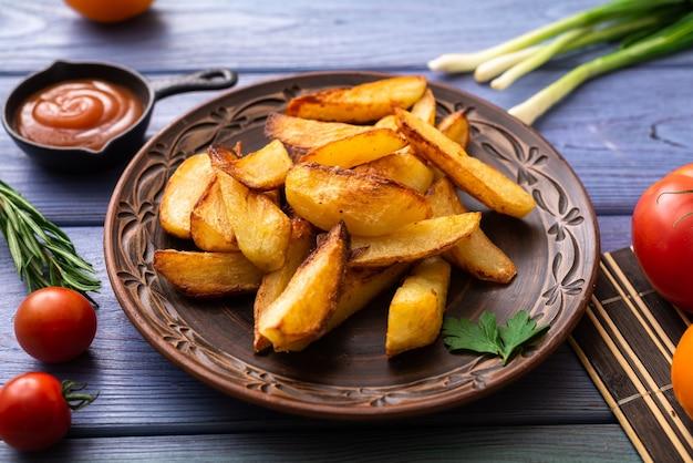 Smażone ziemniaki w dużych kawałkach na talerzu na stole z różnymi warzywami.