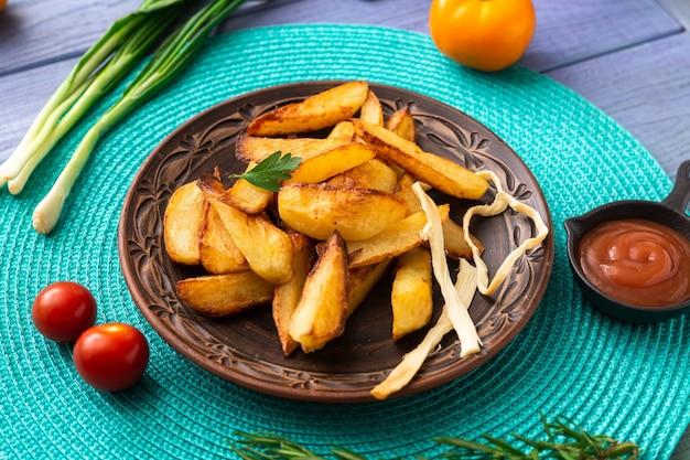 Smażone ziemniaki w dużych kawałkach na talerzu na turkusowej serwetce na stole z różnymi warzywami.