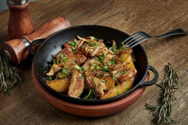 Smażone ziemniaki z boczkiem, cebulą i ziołami na ozdobnej patelni na drewnianej powierzchni. z bliska, selektywne focus.