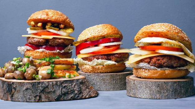 Smażone ziemniaki z pieczarkami i soczystych mięsnych hamburgerów na drewnianych pniach na szarym tle. leśne fast foody.