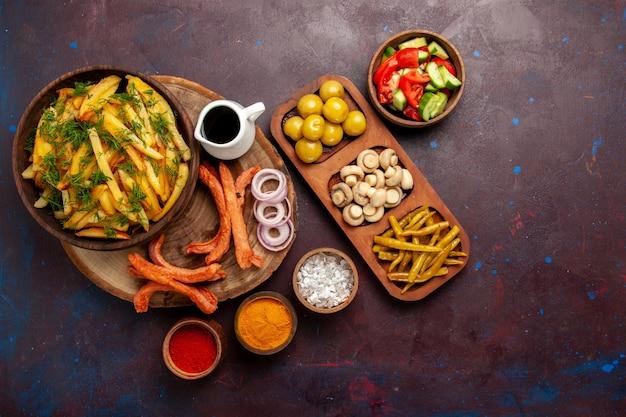Smażone ziemniaki z widokiem z góry smaczne frytki z kiełbaskami i różnymi przyprawami na ciemnym biurku