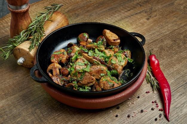 Smażone ziemniaki z wieprzowiną, cebulą i ziołami na ozdobnej patelni na drewnianej powierzchni. ścieśniać