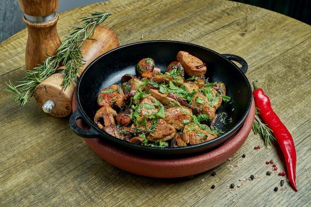 Smażone ziemniaki z wieprzowiną, cebulą i ziołami na ozdobnej patelni na. widok z góry na smaczne jedzenie.