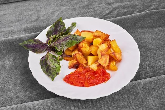 Smażone ziemniaki z ziołami na białym talerzu.