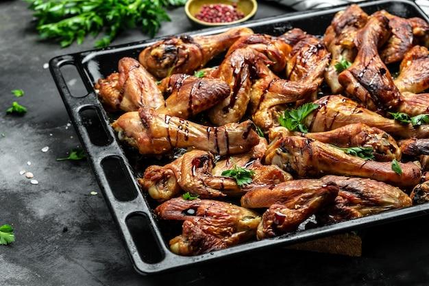 Smażone złote skrzydełka i udka z kurczaka na blasze do pieczenia