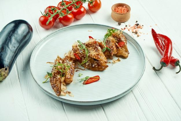 Smażony bakłażan po azjatycku w sosie słodko-kwaśnym z sezamem i ostrą papryczką chili na talerzu ceramicznym na drewnianym stole.