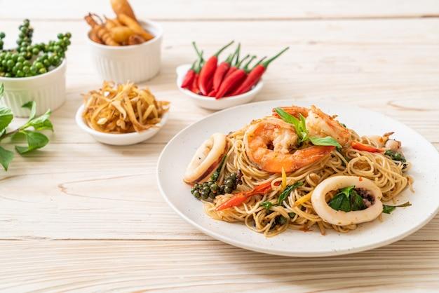 Smażony chiński makaron z bazylią, chilli, krewetkami i kalmarem, azjatyckie jedzenie