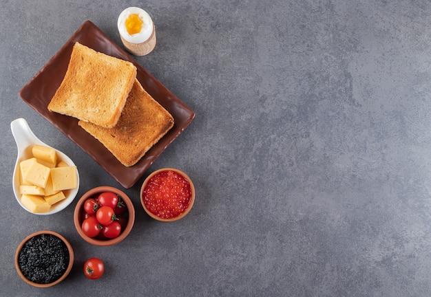 Smażony chleb krojony z czerwonymi pomidorkami cherry i jajkiem na twardo umieszczony na kamiennym tle.