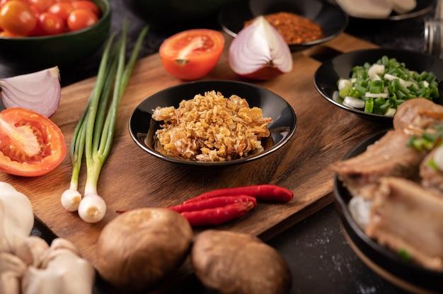 Smażony czosnek na czarnym talerzu z chili, pomidorem i shiitake.