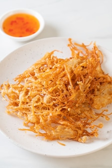 Smażony enoki mushroom lub golden needle mushroom - jedzenie wegańskie i wegetariańskie