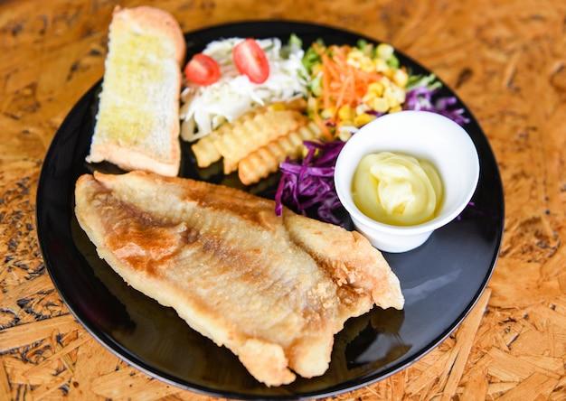 Smażony filet rybny - danie rybne stek rybny z sosem śmietanowo-frytkowym chlebem