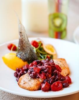 Smażony filet rybny doprawiony gotowanym sosem z granatów na wierzchu