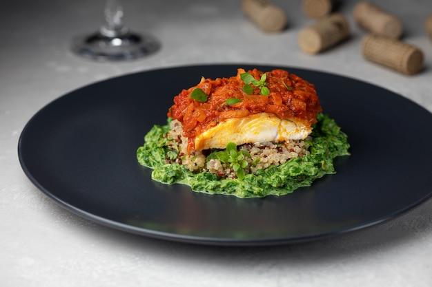 Smażony filet z dorsza (plamiaka) z komosą ryżową, marchewką, cebulą, pomidorami i kremowym szpinakiem na ciemnym talerzu.