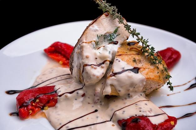 Smażony filet z kurczaka, z białym sosem, gałązką rozmarynu i plasterkami pieczonego pomidora, papryki, na białym talerzu, na czarnym tle