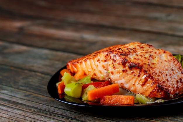 Smażony filet z łososia z azjatyckimi warzywami na czarnym talerzu. zdrowe jedzenie.
