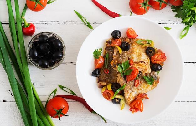 Smażony filet z morszczuka z pomidorami i oliwkami w stylu śródziemnomorskim. widok z góry