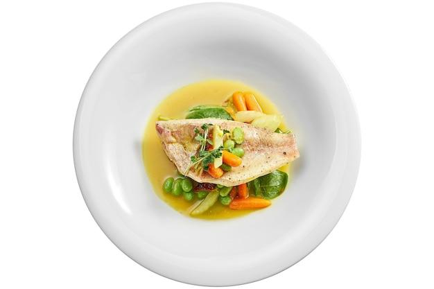 Smażony filet z okonia morskiego z duszonymi warzywami i sosem pomarańczowym w białym talerzu. na białym tle na białej powierzchni. widok z góry