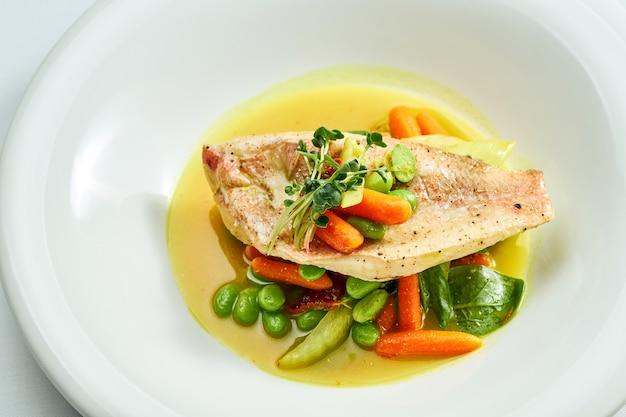 Smażony filet z okonia morskiego z duszonymi warzywami i sosem pomarańczowym w białym talerzu. na białym tle na szarej powierzchni.