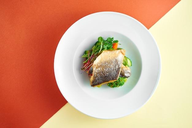 Smażony filet z okonia morskiego z warzywami gotowanymi na parze do dekoracji w białym talerzu na kolorowej powierzchni.