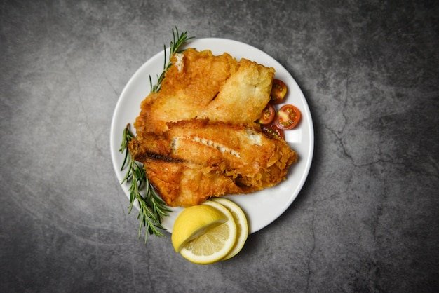 Smażony filet z ryby pokrojony na stek lub sałatkę do gotowania żywności z przyprawami ziołowymi rozmarynem i cytryną - filet z ryby tilapia chrupiący podawany na białym talerzu i ciemnym tle
