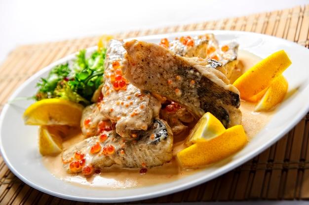 Smażony filet z ryby z frytkami na białym talerzu.