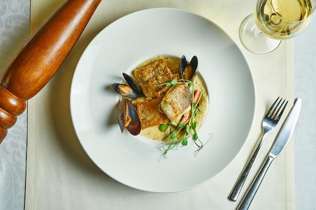 Smażony filet z sandacza w sosie śmietanowym i małże w białej misce. restauracja serwująca dania. owoce morza na lunch