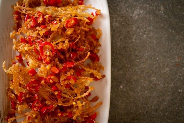Smażony grzyb enoki lub grzyb golden needle z solą i chilli - jedzenie wegańskie i wegetariańskie