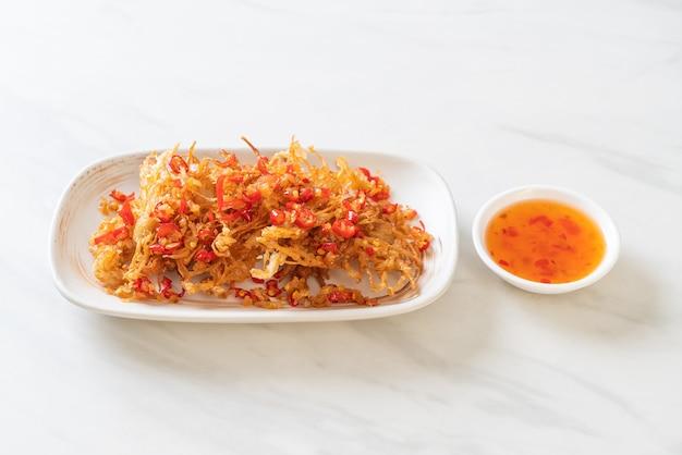 Smażony grzyb enoki lub grzyb złocisty z solą i chilli