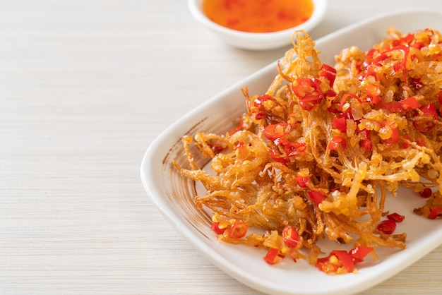 Smażony grzyb enoki lub grzyb złotej igły z solą i chilli. wegański i wegetariański styl jedzenia