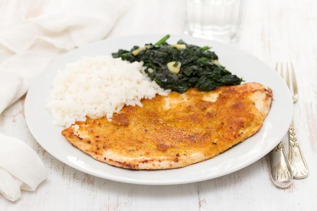 Smażony indyk z ryżem i szpinakiem na talerzu