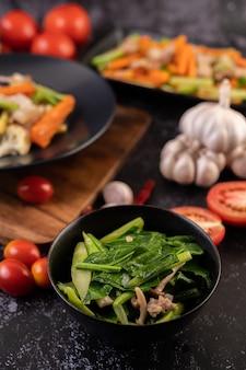 Smażony jarmuż i boczek wieprzowy na talerzu umieszczonym na drewnianym talerzu.
