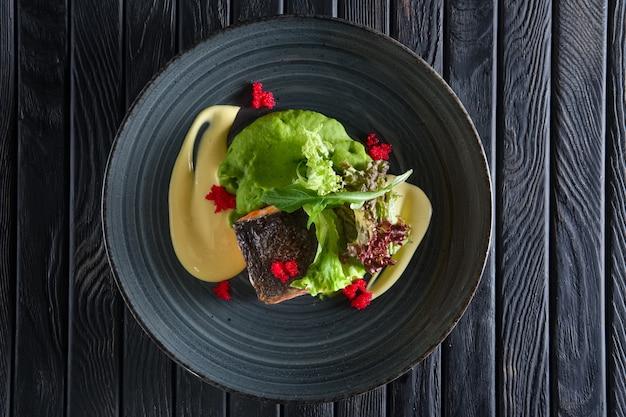 Smażony kawałek łososia z kremowym sosem i zielonymi liśćmi sałatki ozdobiony kawiorem
