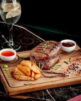 Smażony kawałek mięsa i frytki z sosami