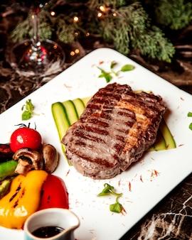 Smażony kawałek mięsa i warzywa ze smażonymi grzybami