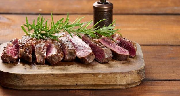 Smażony kawałek ribeye wołowego, pokrojony na kawałki na brązowej drewnianej desce, rzadkie wysmażenie