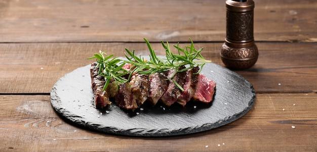 Smażony kawałek ribeye wołowego pokrojony na kawałki na czarnej desce, rzadki stopień wysmażenia. pyszny stek, baner