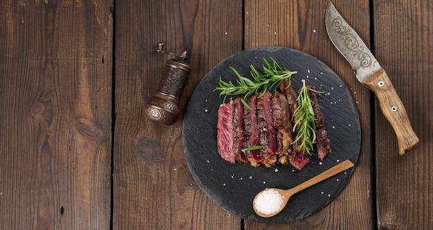 Smażony kawałek ribeye wołowego pokrojony na kawałki na czarnej desce, rzadki stopień wysmażenia. pyszny stek, kopia przestrzeń